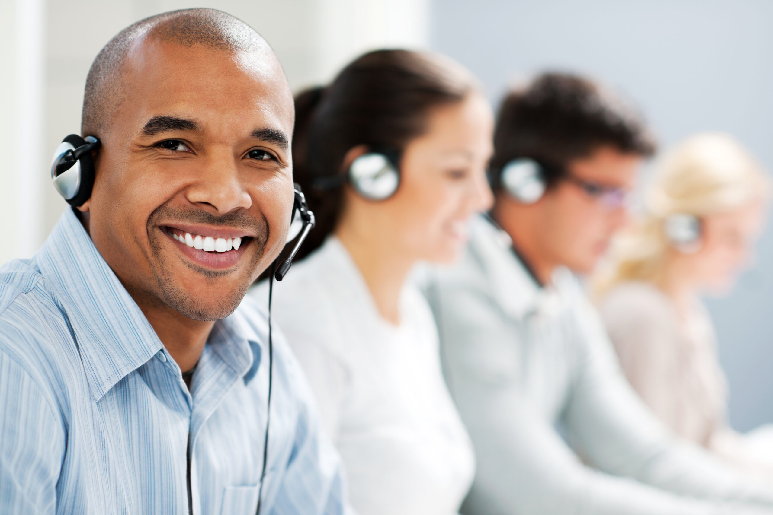 Group of confident young customer service agents with headset. The focus is on the African man looking at camera.